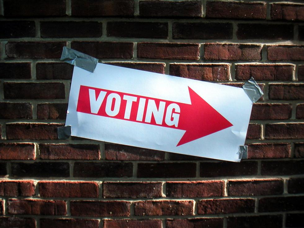 """voting"" sign points to polling station"